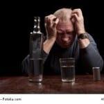 Dark portrait of a man holding his head in despair
