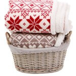 Warm plaids in basket isolated on white