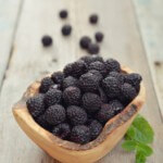 Blackberry in wooden bowl on wood background closeup