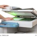 Kopiergerät im Einsatz: Hände legen ein Blatt Papier ins Gerät