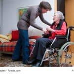 Seniorin im Rollstuhl mit Betreuerin